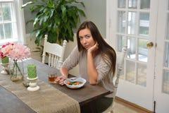 Deprimierte schauende junge Frau, die allein isst Lizenzfreie Stockbilder