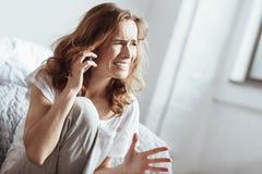 Deprimierte schreiende Frau bei der Unterhaltung am Telefon Stockfotos