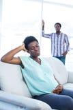 Deprimierte schwangere Frau, die auf Sofa sitzt Lizenzfreie Stockfotografie