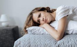 Deprimierte schwermütige Frau, die auf einem Kissen liegt Stockfotos