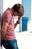 Deprimierte Stellung des jungen Mannes Stockbild
