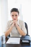 Deprimierte stilvolle Brunettegeschäftsfrau, die ihren Händen sich anschließt lizenzfreies stockbild