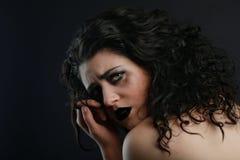 Deprimierte traurige denkende Frau auf schwarzem Hintergrund Stockfoto
