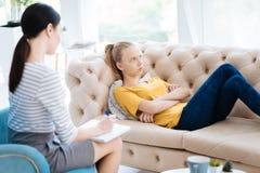 Deprimierte traurige Frau, die auf dem Sofa liegt Lizenzfreies Stockbild