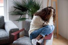 Deprimierte traurige Frau halten Haupt in den Händen, die auf Lehnsessel sitzen Lizenzfreie Stockfotografie