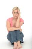 Deprimierte traurige unglückliche junge Frau, die allein auf dem Boden schaut gebohrt sitzt Lizenzfreies Stockfoto