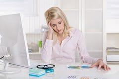 Deprimierte und frustrierte junge Geschäftsfrau, die am Schreibtischesprit sitzt Lizenzfreie Stockfotografie