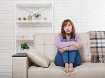 Deprimierte und traurige mittlere Greisin, die zu Hause mit festgeklemmten Knien auf Bett, Trainer, Sofa sitzt Kopieren Sie Raum  Lizenzfreie Stockbilder