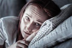 Deprimierte unglückliche Frau, die auf Kissen weint Stockbild