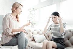 Deprimierte unglückliche Frau, die zum Kopf spricht und sich berührt Stockfotografie