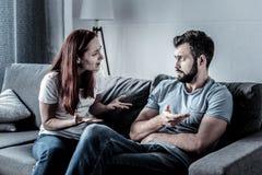 Deprimierte verärgerte Frau, die mit ihrem Ehemann gestikuliert und spricht Stockfoto