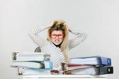 Deprimierte verärgerte Geschäftsfrau, die am Schreibtisch sitzt Stockfoto