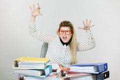 Deprimierte verärgerte Geschäftsfrau, die am Schreibtisch sitzt Lizenzfreie Stockfotos