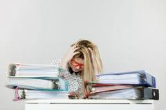 Deprimierte verärgerte Geschäftsfrau, die am Schreibtisch sitzt Stockbild
