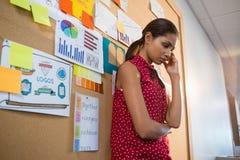 Deprimierte weibliche Exekutive, die nahes Anschlagbrett steht Stockfotos