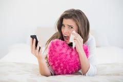 Deprimierte zufällige braune behaarte Frau in den weißen Pyjamas, die herauf ihren Handy hängen Lizenzfreie Stockfotos