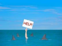 Deprimierten Mann mit dem Hilfszeichen ertrinken umgeben durch Haifische lizenzfreies stockbild