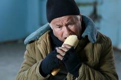 Deprimierter älter-gealterter Bettler, der Brot isst Stockfotos