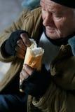 Deprimierter älter-gealterter Bettler, der Brot isst Lizenzfreies Stockfoto
