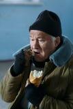 Deprimierter älter-gealterter Bettler, der Brot isst Stockbilder