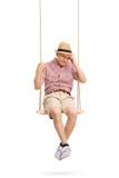 Deprimierter älterer Mann, der auf einem Schwingen sitzt Stockbilder