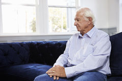 Deprimierter älterer Mann, der auf Sofa At Home sitzt Lizenzfreies Stockbild