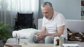 Deprimierter älterer Mann, der auf Sofa am Pflegeheim, an der Einsamkeit und an der Melancholie sitzt Lizenzfreies Stockbild