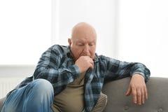 Deprimierter älterer Mann, der auf Sofa sitzt Stockfotos