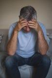 Deprimierter älterer Mann, der auf Sofa sitzt Stockfotografie