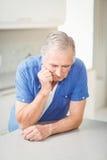 Deprimierter älterer Mann, der auf Tabelle sich lehnt Stockfotos