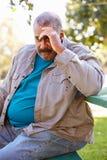 Deprimierter älterer Mann, der draußen sitzt Lizenzfreies Stockbild