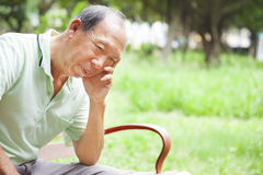 Deprimierter älterer Mann, der im Park sitzt Lizenzfreie Stockbilder