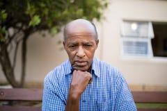 Deprimierter älterer Mann, der mit der Hand auf Kinn sitzt Lizenzfreies Stockfoto