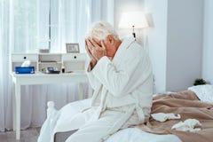 Deprimierter älterer Mann, der unter Krankheit leidet Lizenzfreie Stockfotos