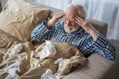 Deprimierter älterer Mann, der unter Migräne leidet Lizenzfreie Stockfotografie