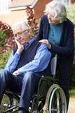 Deprimierter älterer Mann im Rollstuhl, der von der Frau gedrückt wird Lizenzfreie Stockfotos