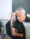 Deprimierter älterer Student Looking At Computer Lizenzfreie Stockfotografie