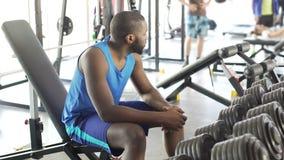 Deprimierter afro-amerikanischer Mann, der in der Turnhalle sitzt und an Probleme denkt stock video