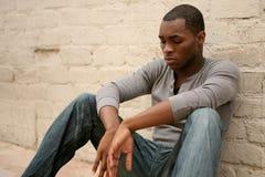Deprimierter Afroamerikaner-Mann, der am Al sich lehnt Stockbild