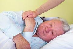 Deprimierter alter Mann im Bett Stockfotos