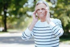 Deprimierter Alternmann, der draußen den schrecklichen Schmerz im Kopf glaubt Stockbilder