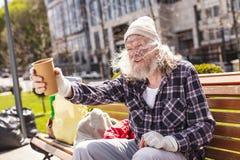 Deprimierter armer Mann, der auf der Bank sitzt Stockbild