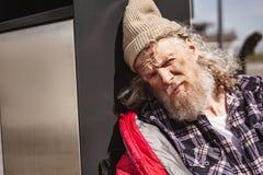 Deprimierter armer Mann, der sich an zum Sänftenbehälter lehnt Stockfoto