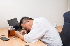 Deprimierter asiatischer Geschäftsführer getrunken auf Schreibtisch Stockbilder