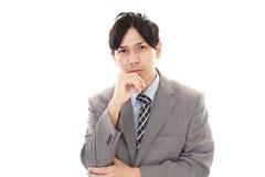 Deprimierter asiatischer Geschäftsmann Stockbild