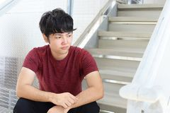 Deprimierter asiatischer Mann Stockbild