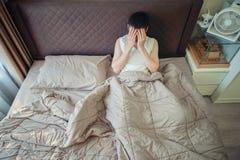 Deprimierter asiatischer Mann, der am Telefon auf Bett tadelt Stockfotografie
