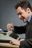 Deprimierter Autor, der an der Schreibmaschine sitzt Lizenzfreie Stockfotos