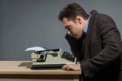 Deprimierter Autor, der an der Schreibmaschine sitzt Stockbilder