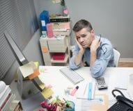 Deprimierter Büroangestellter an seinem Schreibtisch Lizenzfreie Stockbilder